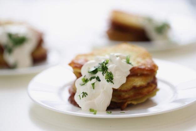 Картофельные оладьи со сметаной и зеленью на тарелке, готовя концепцию здорового завтрака