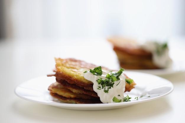 Картофельные оладьи со сметаной и зеленью на белой тарелке, готовя концепцию вегетарианской еды
