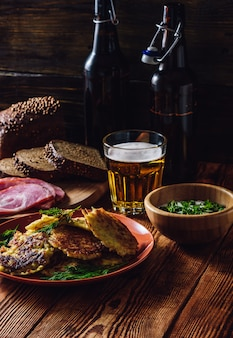 Potato pancakes with sour cream, greens, smoked meat and glass of beer