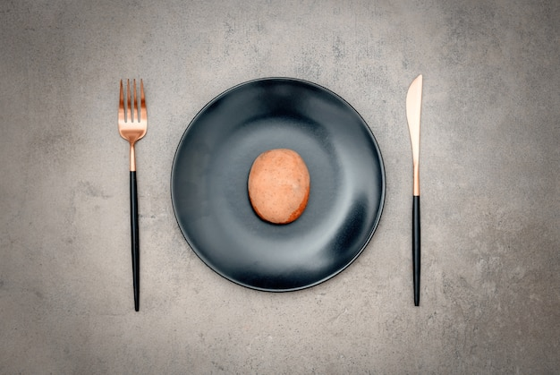 Potato in a plate with knife and fork