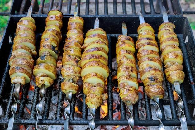 Картофельные шашлычки на горящих углях на гриле.