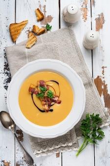 Картофельный суп-крем с беконом и соевым соусом в белой миске, на светлой старой деревянной поверхности