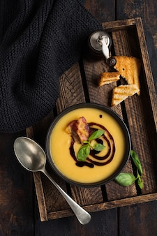 Potato soup cream with bacon and soy sauce in black bowl, on dark old concrete surface