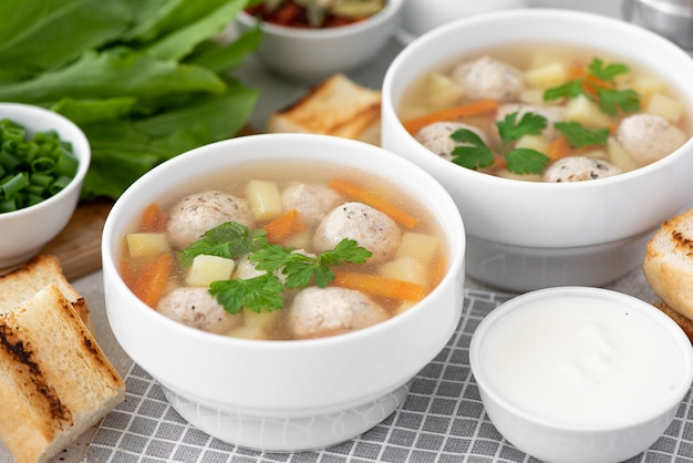 Potato soup with meatballs, carrots and herbs