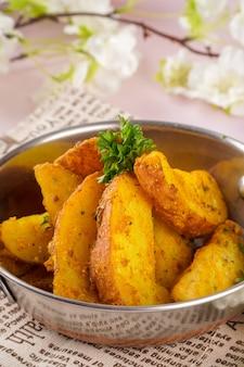 웨지 감자는 종종 크고 껍질이 벗겨지지 않은 불규칙한 쐐기 모양의 감자 조각입니다.