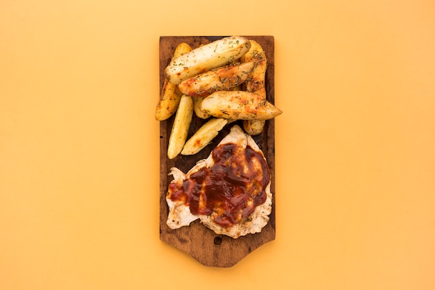 Potato wedges and meat with sauce on wooden board