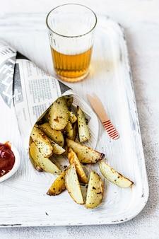 Картофельные дольки с пивом на подносе