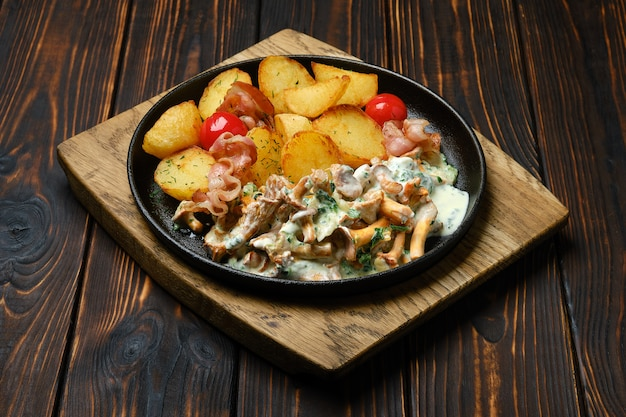 Potato wedges with chanterelles and pork in cast iron skillet