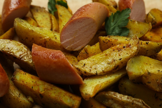 Potato wedges with spices and fried sausage, close up