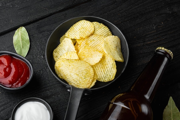 Potatoe chips set, and bottle of beer, on black wooden table, top view flat lay