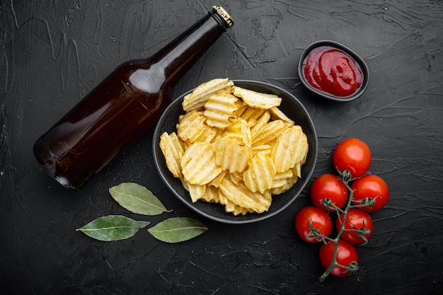 Potatoe chips set, with bottle of beer, on black stone table, top view flat lay