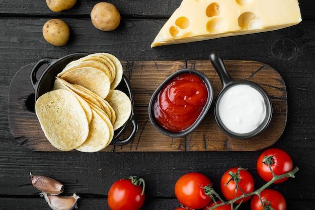 チーズと玉ねぎをセットしたポテトチップス、黒い木製のテーブル、上面図フラットレイ