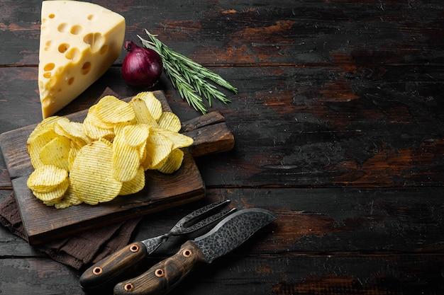 오래 된 어두운 나무 테이블에 치즈와 양파로 설정된 potatoe 칩