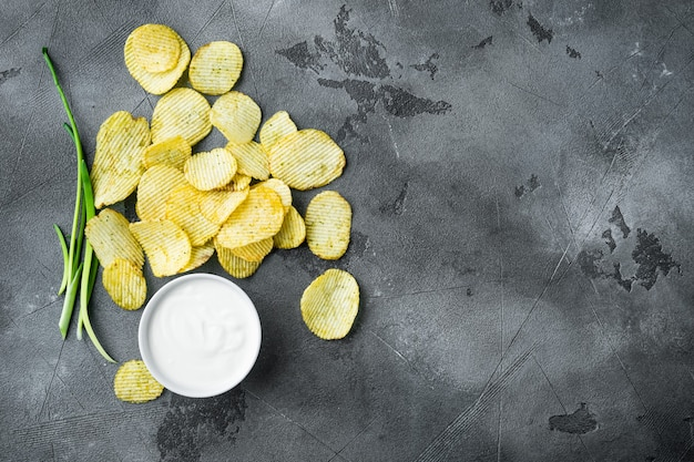 Potatoe chips set, with dipping sauces, on gray stone table, top view flat lay