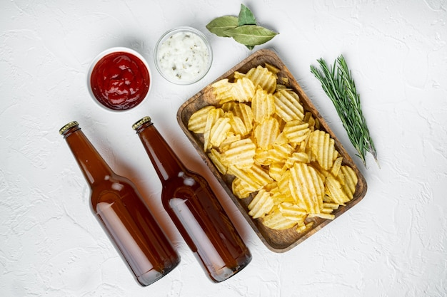 Potatoe chips set, with dipping sauces tomato dip sour cream, and bottle of beer, on white stone