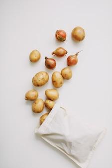 白い有機健康食品表面のエコバッグにジャガイモとタマネギ