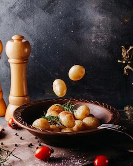 Картофель отварной соленый внутри коричневой круглой пластины на серой поверхности
