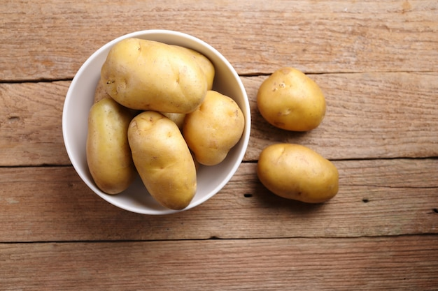 Potatoes in bowl on wooden background