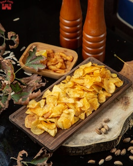 Potatoes chips and spice grinders on the table