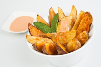 Potatoes cut into wedges and bowl of sauce