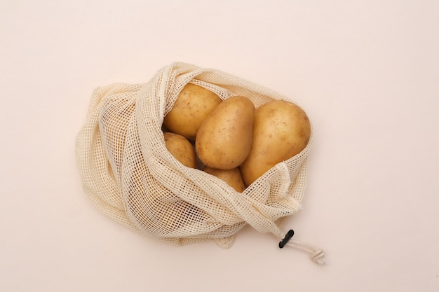 Potatoes in eco cotton bag on beige background. top view. flat lay