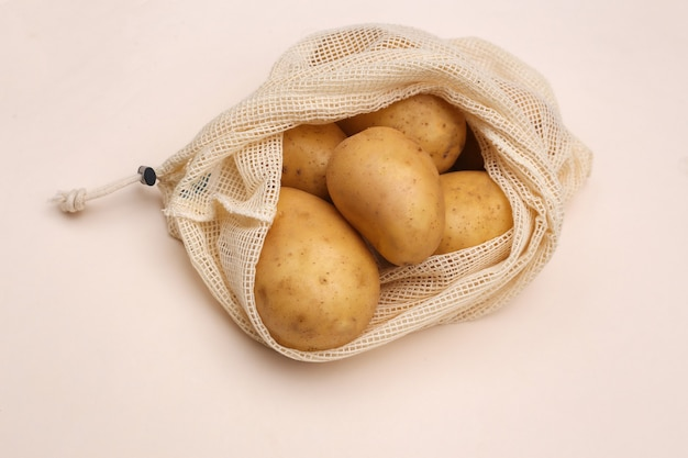 Potatoes in eco cotton bag on beige background