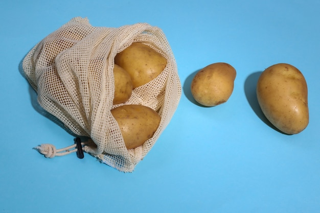 Potatoes in eco cotton bag on blue bright background