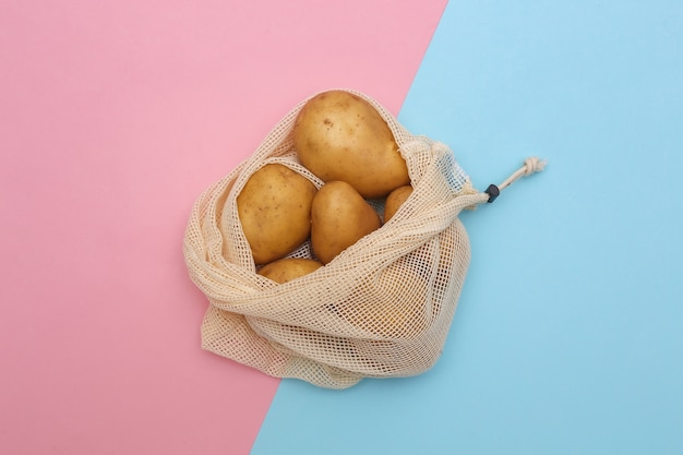 Potatoes in eco cotton bag on pink blue pastel background