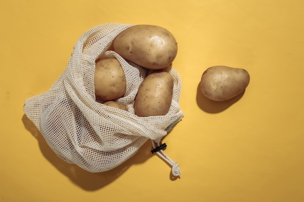 Potatoes in eco cotton bag on yellow bright background