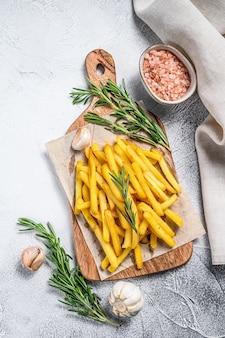 Картофель фри, картофель фри с розмарином на разделочной доске