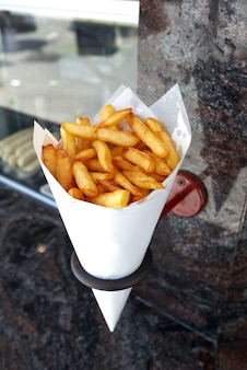 Potatoes fries in a little white paper bag hanging at the wall from a belgian friterie