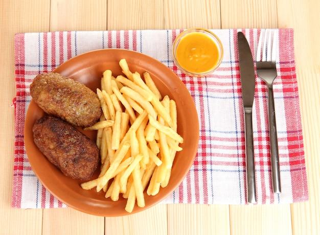 木製のテーブルのクローズアップのプレートにハンバーガーとジャガイモのフライドポテト