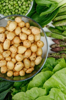 Potatoes in a glass bowl with green pods, peas, spinach, sorrel, lettuce, asparagus top view on a white wall