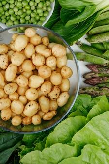 Patate in una ciotola di vetro con baccelli verdi, piselli, spinaci, acetosa, lattuga, asparagi vista dall'alto su un muro bianco