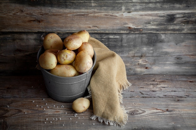 Potatoes in a gray bucket side view on a dark wooden background space for text