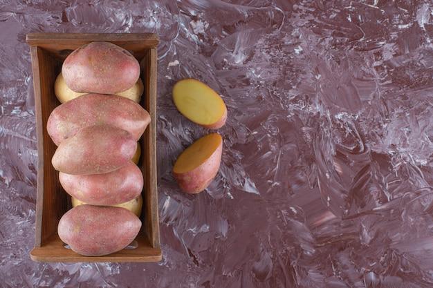 大理石の背景に、木製の箱に入ったジャガイモ。