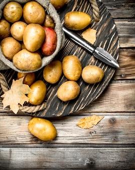 ジャガイモの皮むき器が付いている皿の袋のジャガイモ。