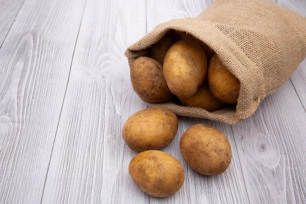 Картофель, изолированные в джутовом мешке на белом фоне