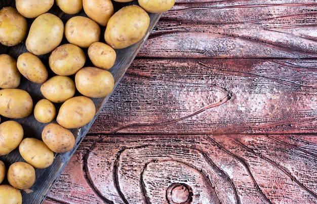 Картофель на ткани сверху на деревянном столе