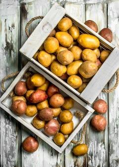Картофель на подносе и в ящике. на белом деревянном столе