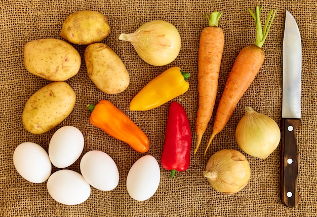 Potatoes, onions, bell peppers, carrots and chicken eggs lie on sackcloth