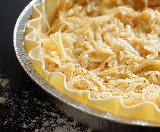 Картофельный пирог в алюминиевой форме на темном фоне крупным планом
