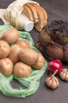 Potatoes in plastic bag. bread and milk in linen bag. onions in black reusable bag.