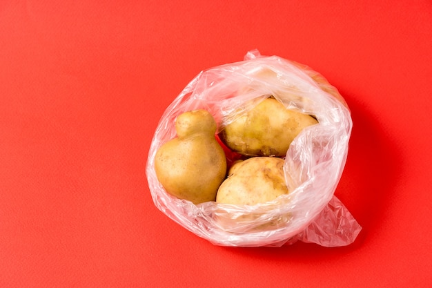 Potatoes in plastic bag on red background. stop using artificial food storage bags.