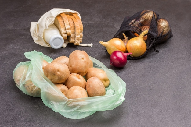 Potatoes in plastic bag with bread and milk in linen bag