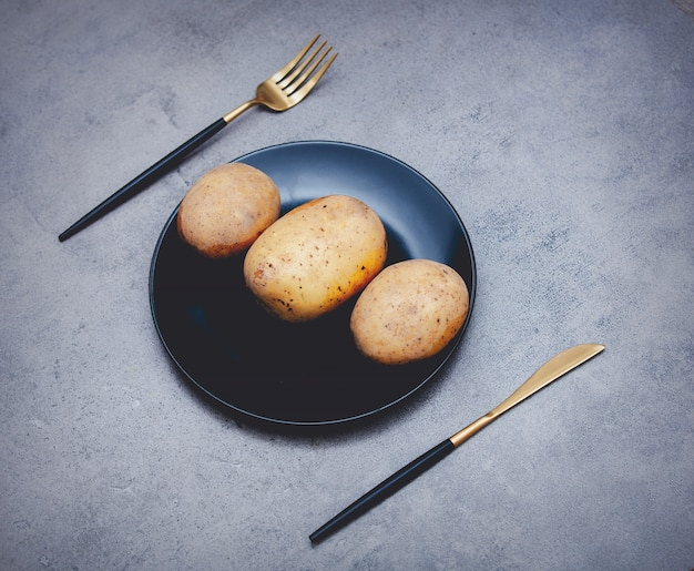 Potatoes in a plate with knife and fork