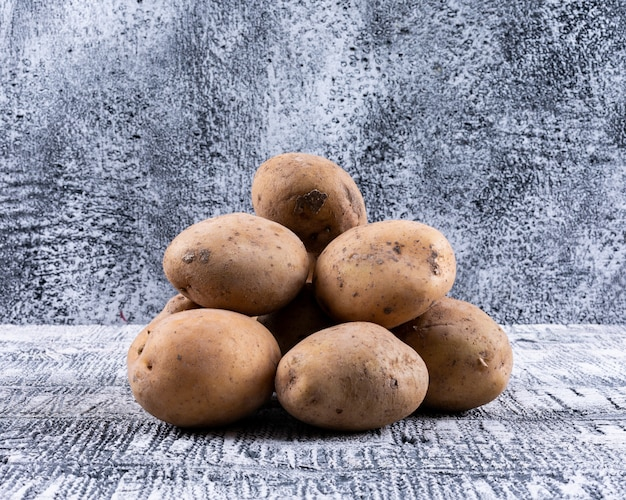 Potatoes in a sack bag side view on a gray wooden table