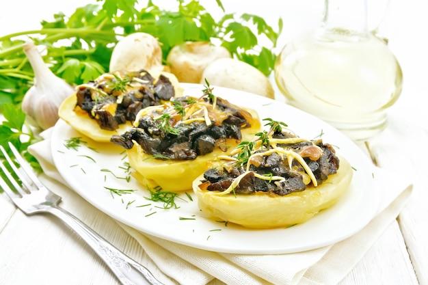 きのこ、揚げタマネギ、チーズをキッチンタオルの皿に詰めたジャガイモ、デカンターの植物油、パセリ、ニンニク、木の板の背景にフォーク