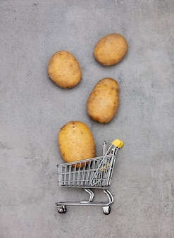 Potatoes and supermarket cart on a table.