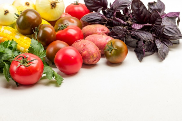감자, 토마토, 양파, 흰색 바탕에 파란색 바시. 테이블에 야채 세트입니다. 공간을 복사합니다. 플랫 레이